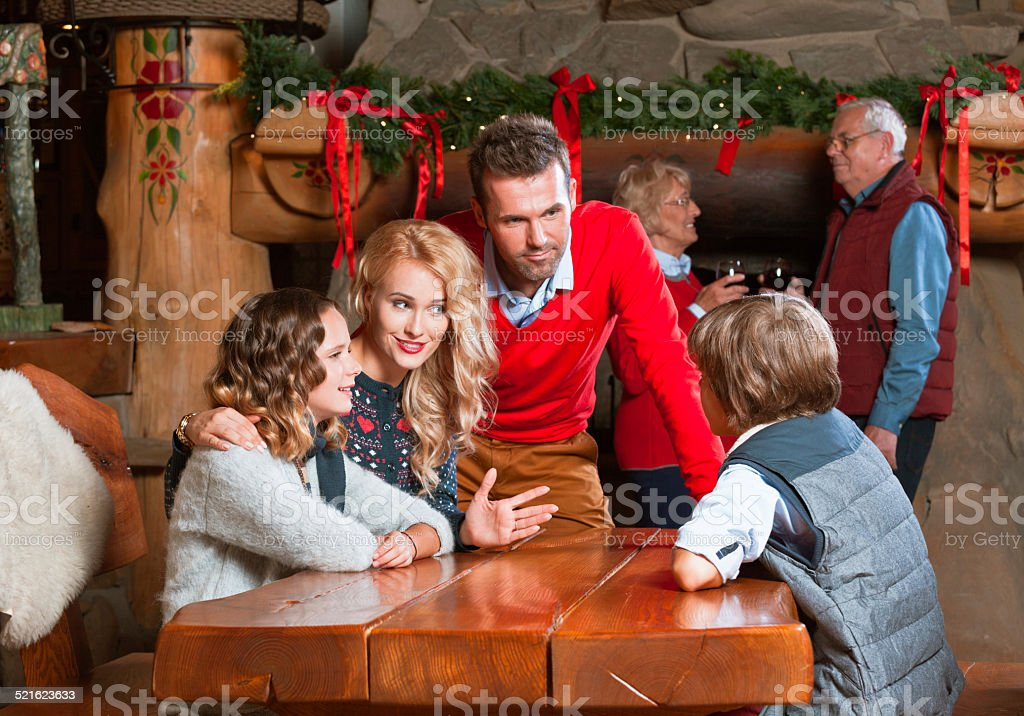 Happy family meeting at Christmas Time Happy parents talking with their children at the table at home with granparents drinking re wine by the fireplace decorated with christmas ornaments. Active Seniors Stock Photo
