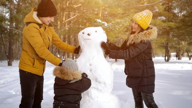 glückliche familie mama, vater und sohn machen einen schneemann im winter stadtpark. - schneemann bauen stock-fotos und bilder