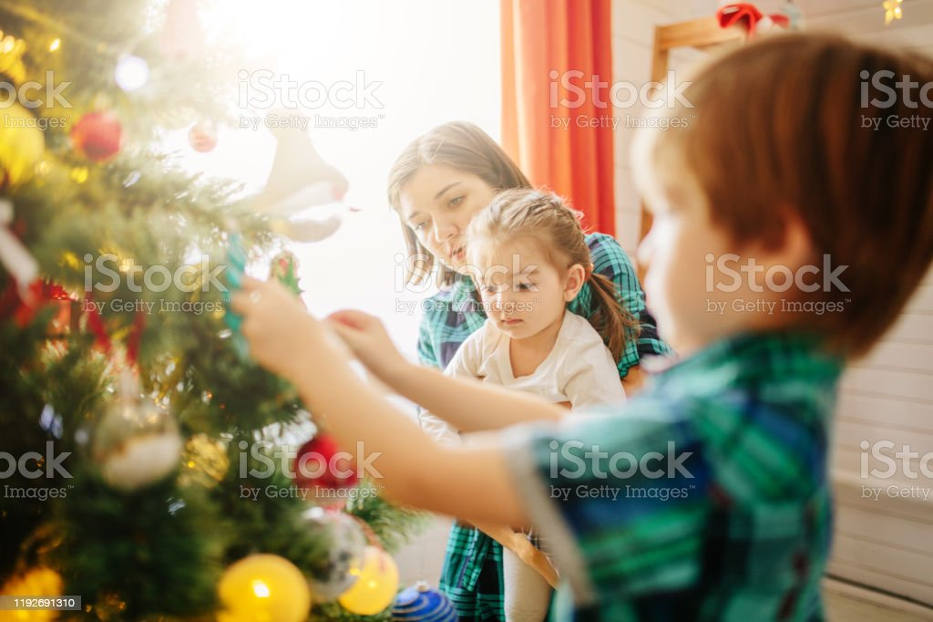 Happy Family Mom Son And Daughter On A Christmas Winter Sunny Morning In A Decorated Christmas Celebration Room With A Xmas Tree And Gifts Stock Photo Download Image Now Istock