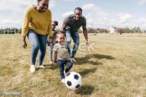 Family with kids playing soccer in soccer field