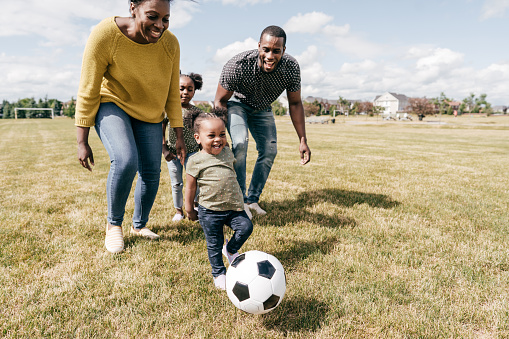 Happy family moments - kids playing soccer with parents