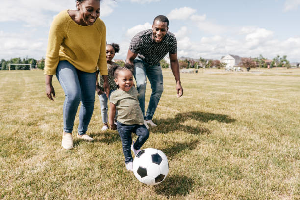 Happy family moments - kids playing soccer with parents stock photo