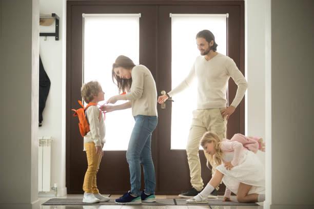 Preparativos de mañana familia feliz, los padres preparando niños para la escuela - foto de stock