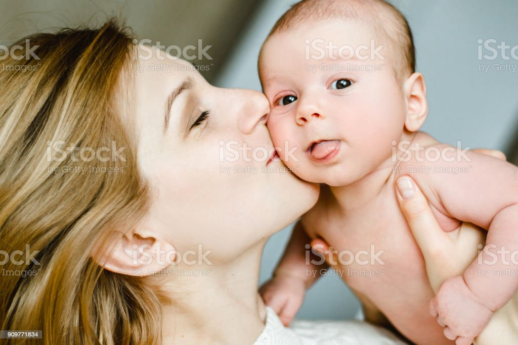happy family mother and baby having fun playing, kissing on the bed stock photo