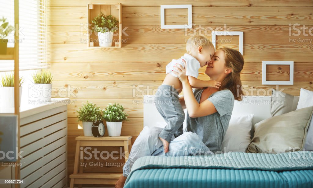 happy family mother and baby son toddler laughing  in bed stock photo