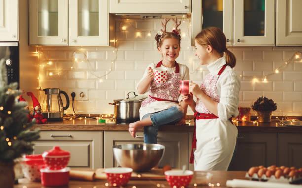 gelukkige familie moeder en kind bakken kerstkoekjes - christmas family stockfoto's en -beelden
