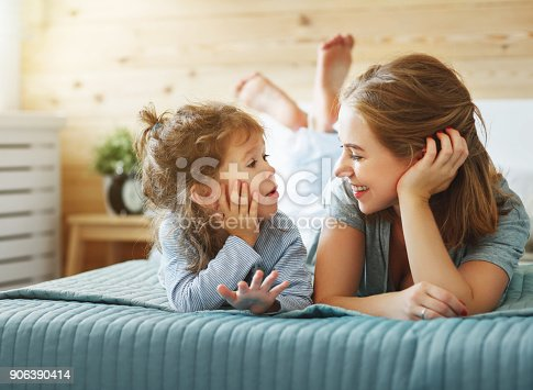 istock Happy family mother and child daughter laughing in bed 906390414