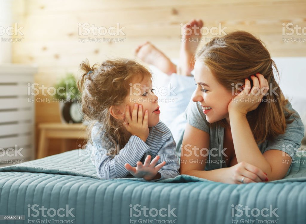 Happy family mother and child daughter laughing in bed stock photo