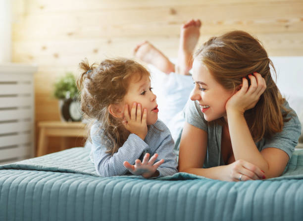 happy family mother and child daughter laughing in bed - daughter stock photos and pictures
