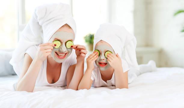 glückliche familie mutter und kind tochter machen haut gesichtsmaske - gurkenmaske stock-fotos und bilder