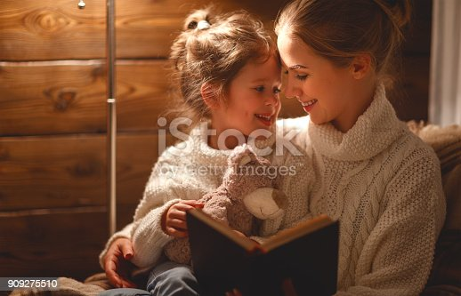 istock happy family mother and child daughter read a book on  winter evening 909275510