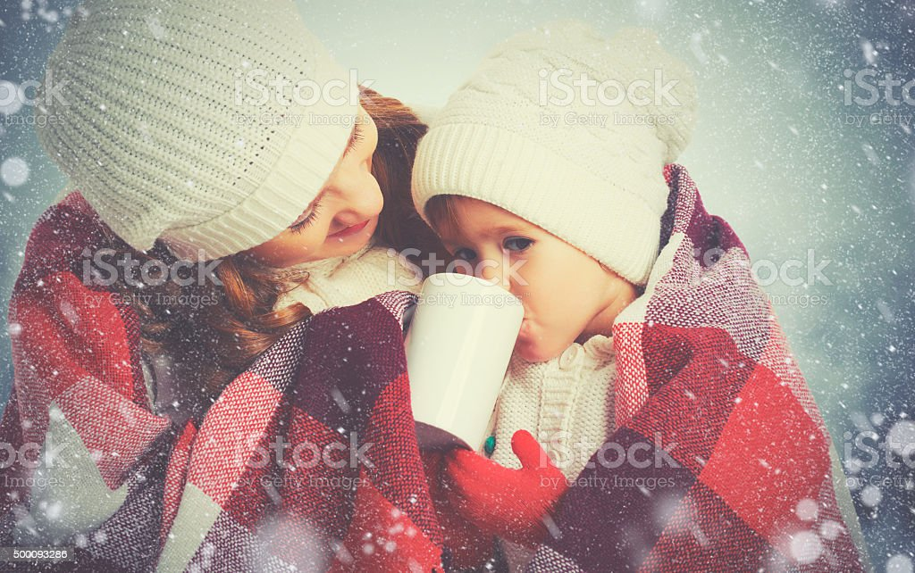 happy family mother and child drinking hot tea on winter stock photo
