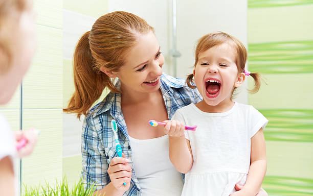 happy family mother and child girl cleans teeth with toothbrush - baby teeth stok fotoğraflar ve resimler