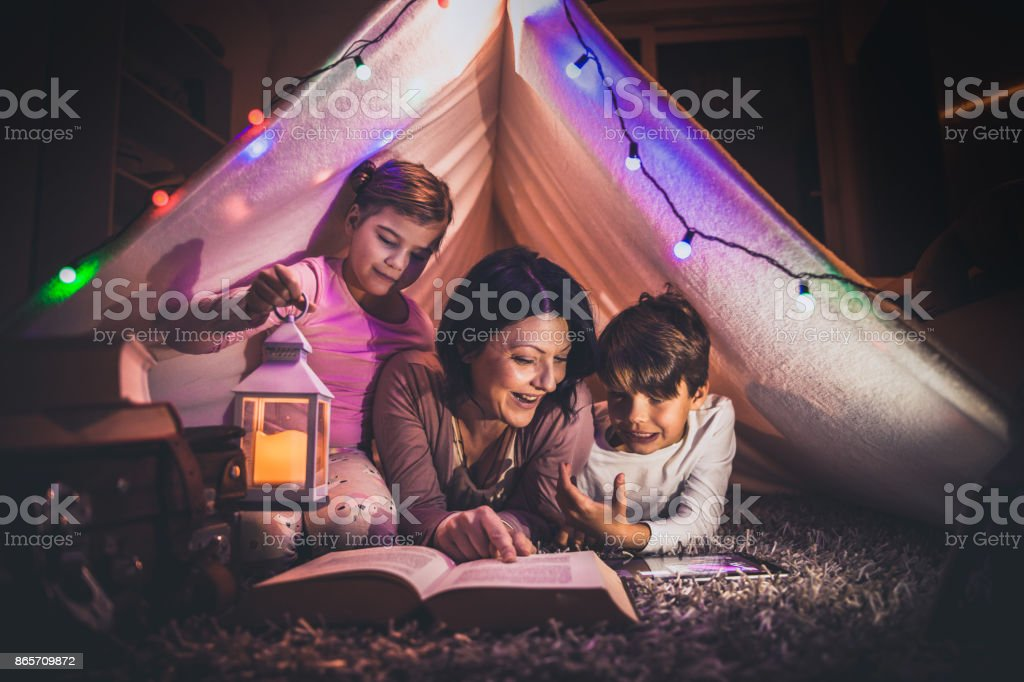 Happy family mother and child reading a book in tent at home stock photo
