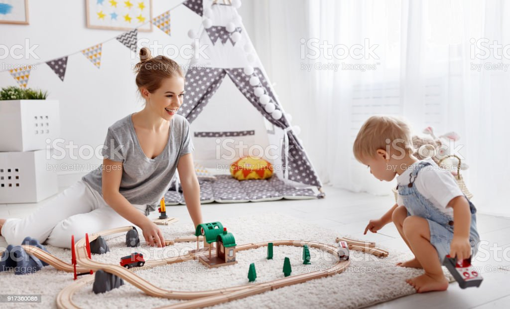 happy family mother and child son playing   in toy railway in playroom