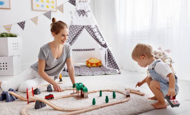 glückliche familie, mutter und kind sohn in spielzeug-eisenbahn im spielzimmer spielen - holzspielwaren stock-fotos und bilder