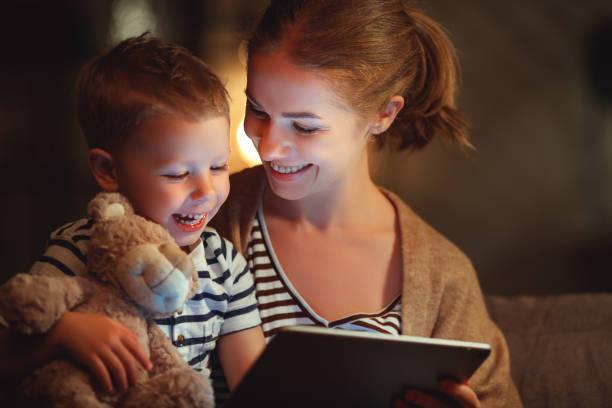 . Glückliche Mutter und Kindersohn mit Tablet am Abend – Foto