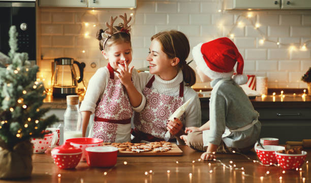 happy family mother and children bake christmas cookies - christmas cooking imagens e fotografias de stock
