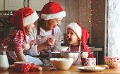 幸せ家族の母親と子供たちはクリスマスのためにクッキーを焼く