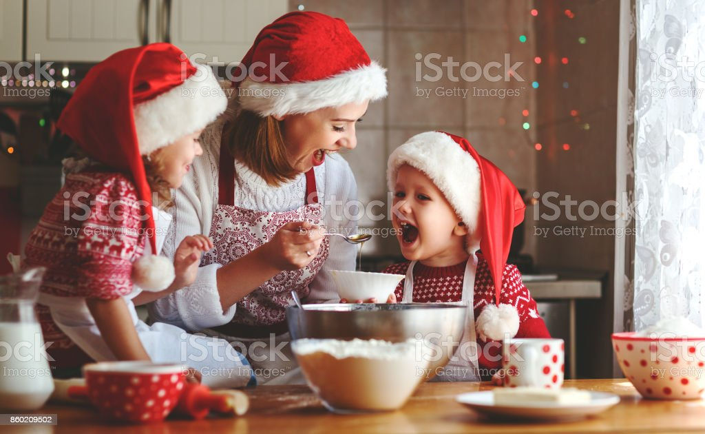 happy family mother and children  bake cookies for Christmas stock photo