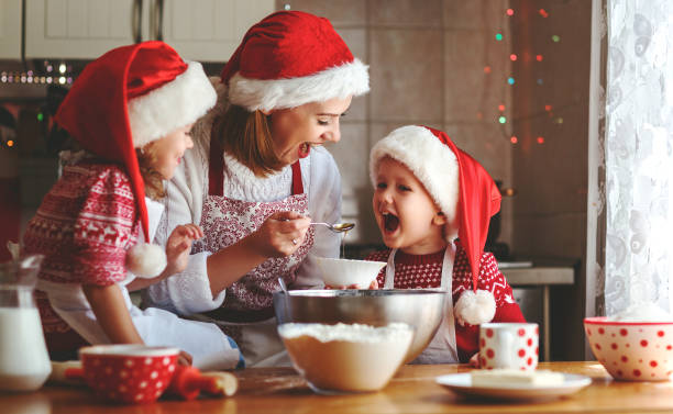 happy family mother and children  bake cookies for christmas - christmas cooking imagens e fotografias de stock