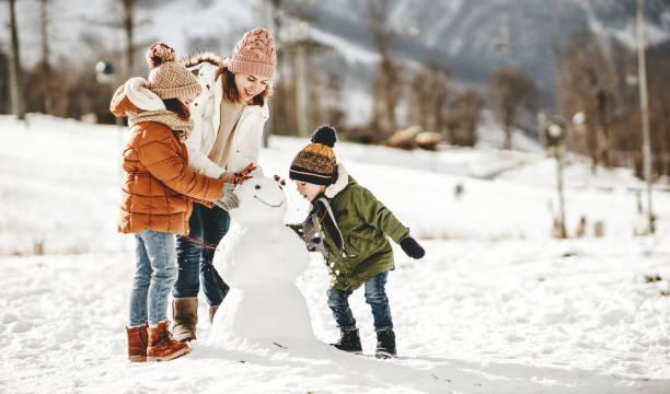 feliz madre de la familia y los niños divirtiéndose en el paseo de invierno - invierno fotografías e imágenes de stock