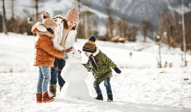 glückliche familie mutter und kinder spaß auf winterspaziergang - winter stock-fotos und bilder