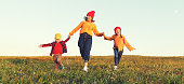 istock happy family mother and children in autumn nature at sunset 1183111031