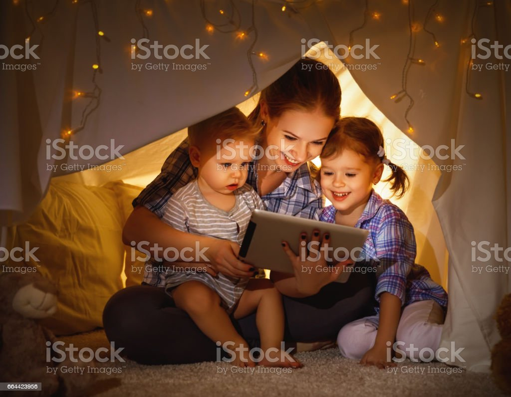 Happy family mother and children playing in tablet  pc stock photo