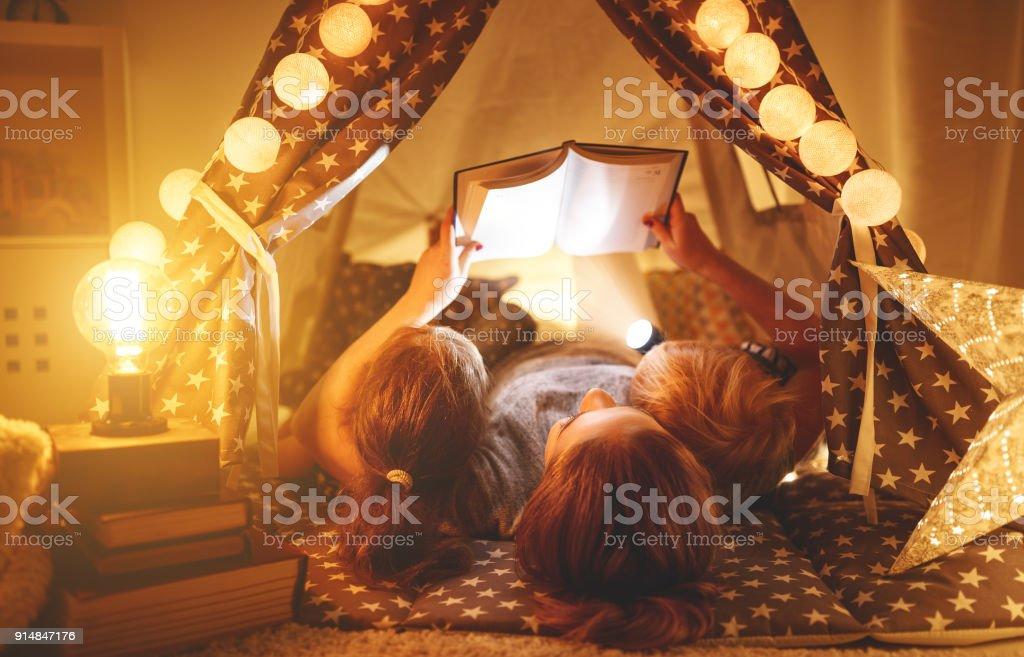 glückliche Familie Mutter und Kinder lesen ein Buch im Zelt zu Hause – Foto