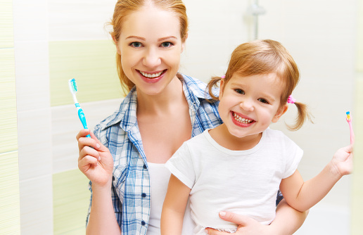 happy family mother and daughter child brushing her teeth stock photo