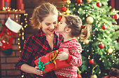 istock happy family mother and daughter giving christmas gift 876420332