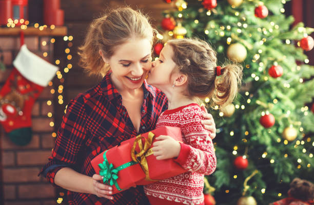 happy family mother and daughter giving christmas gift - christmas background стоковые фото и изображения