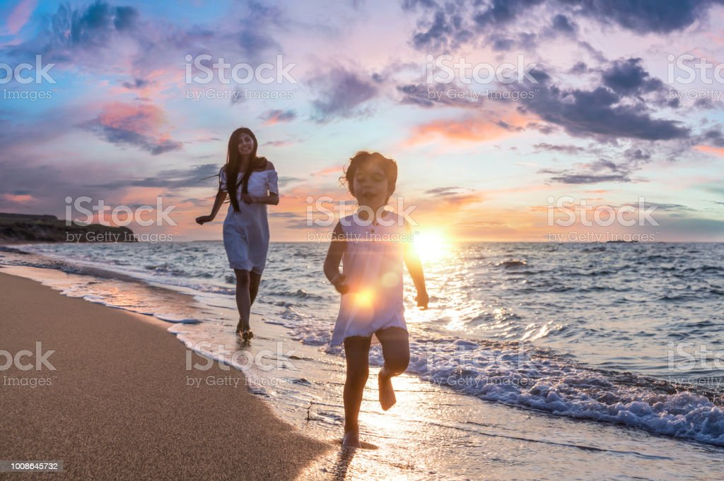 Happy Family Mother And Daughter Run Laugh And Play At Beach