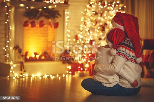 istock happy family mother and daughter sitting  backs near tree on of Christmas 880316230