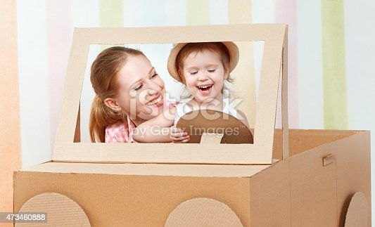 496487362 istock photo Happy family mother and little daughter ride on toy car 473460888