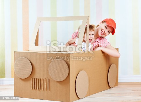 496487362 istock photo Happy family mother and little daughter ride on toy car 473460898