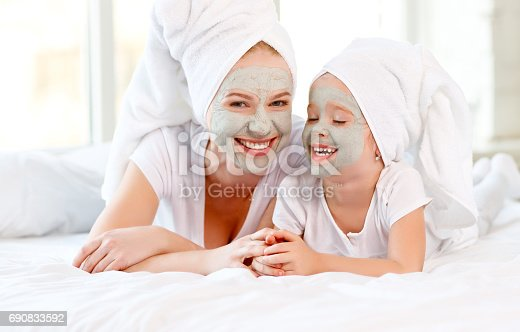 istock Happy family mother and toddler make face skin  mask 690833592