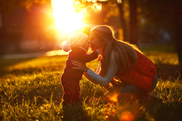 Happy family mother and toddler outdoors in park stock photo