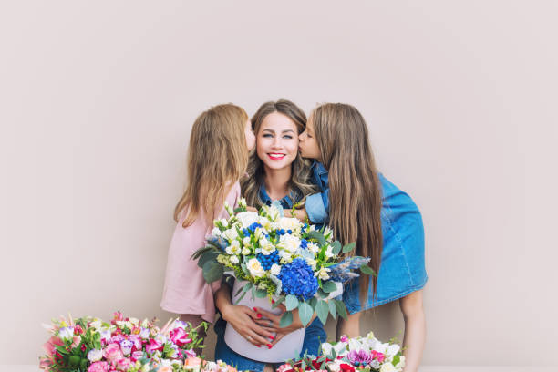 Happy family mother and two beautiful girls daughters on holiday in flowers together on isolated background stock photo