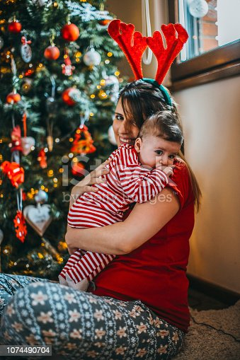 868220646istockphoto Happy family mother father and baby at christmas tree at home 1074490704