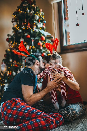 868220646istockphoto Happy family mother father and baby at christmas tree at home 1074492800