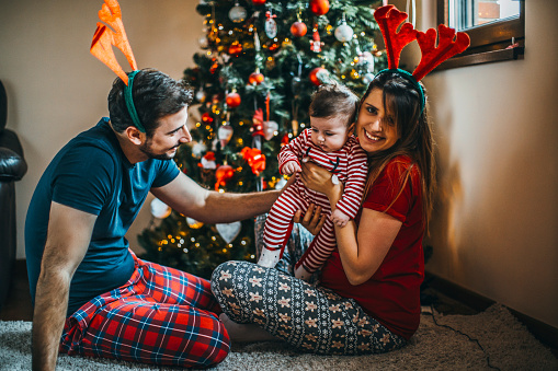 868220646 istock photo Happy family mother father and baby at christmas tree at home 1074492802