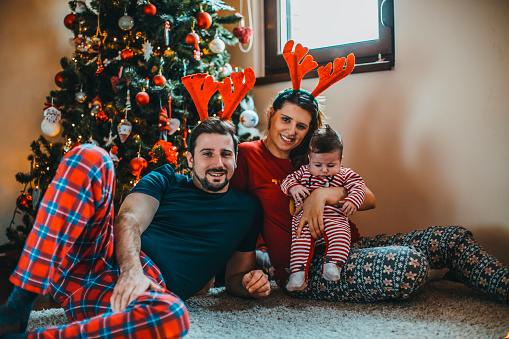 868220646 istock photo Happy family mother father and baby at christmas tree at home 1074497272
