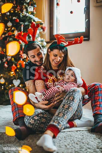868220646istockphoto Happy family mother father and baby at christmas tree at home 1074499768