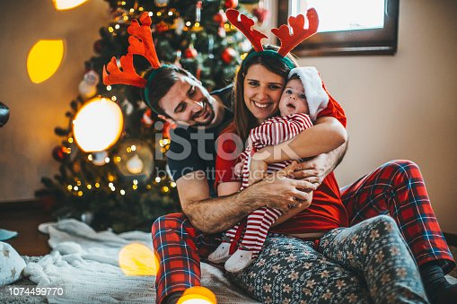 868220646istockphoto Happy family mother father and baby at christmas tree at home 1074499770
