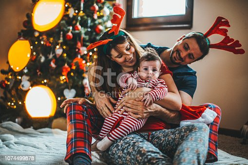868220646istockphoto Happy family mother father and baby at christmas tree at home 1074499878