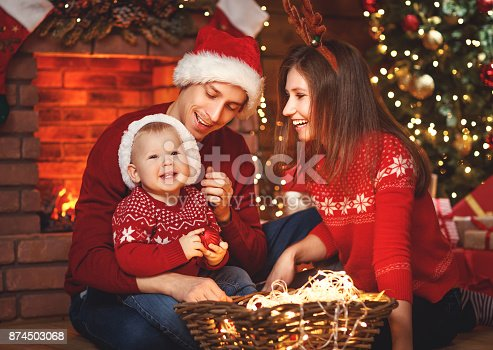 868220646istockphoto happy family mother father and baby at christmas tree at home 874503068