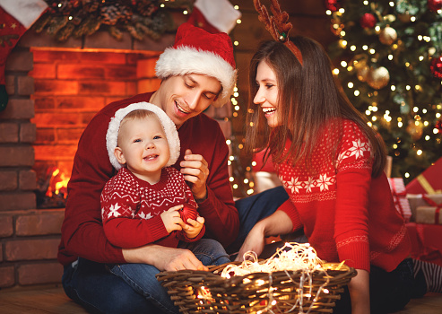 868220646 istock photo happy family mother father and baby at christmas tree at home 874503068