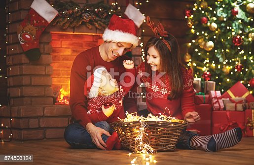 868220646istockphoto happy family mother father and baby at christmas tree at home 874503124